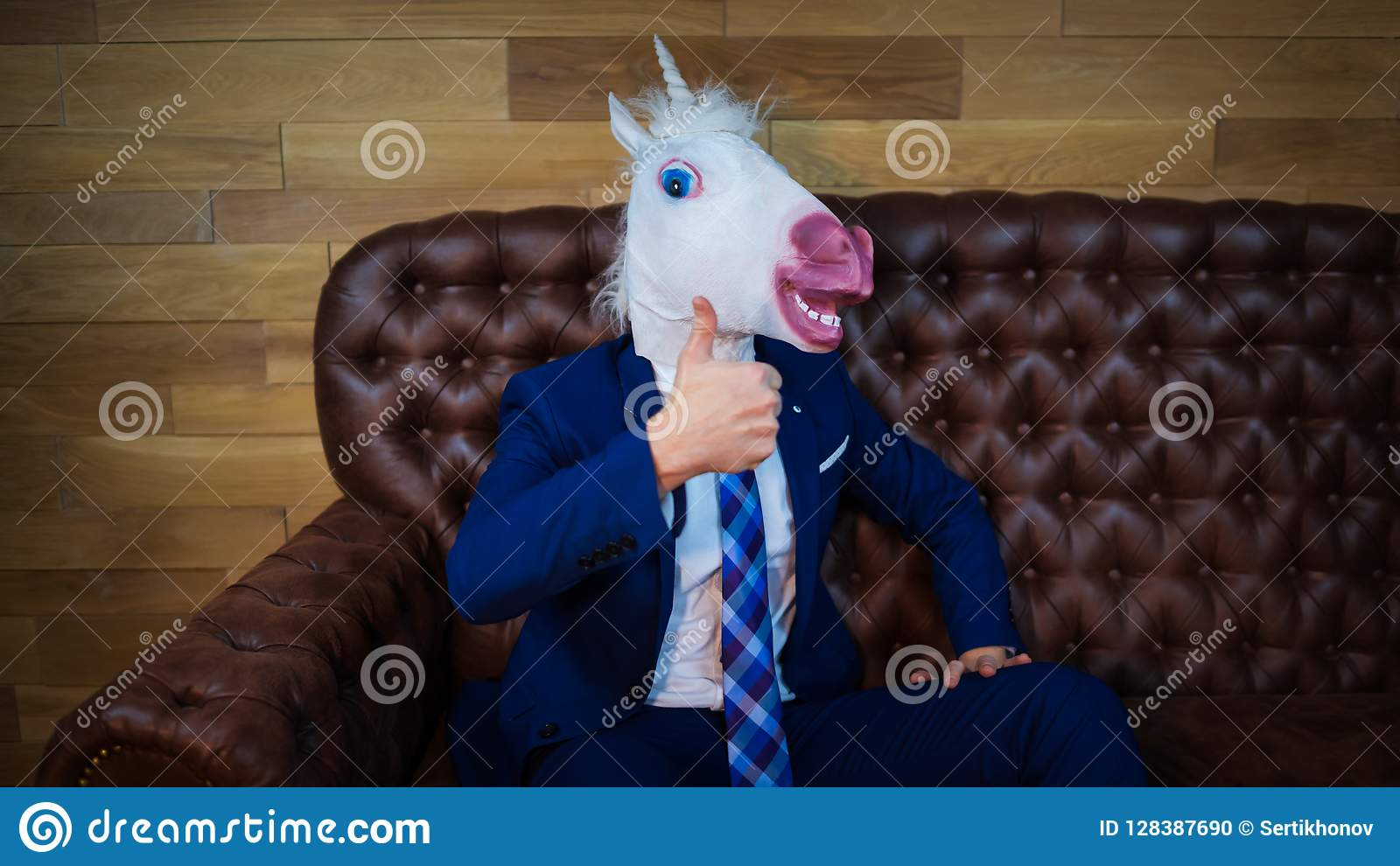 Funny unicorn in elegant suit sits on sofa like a boss and showing gesture