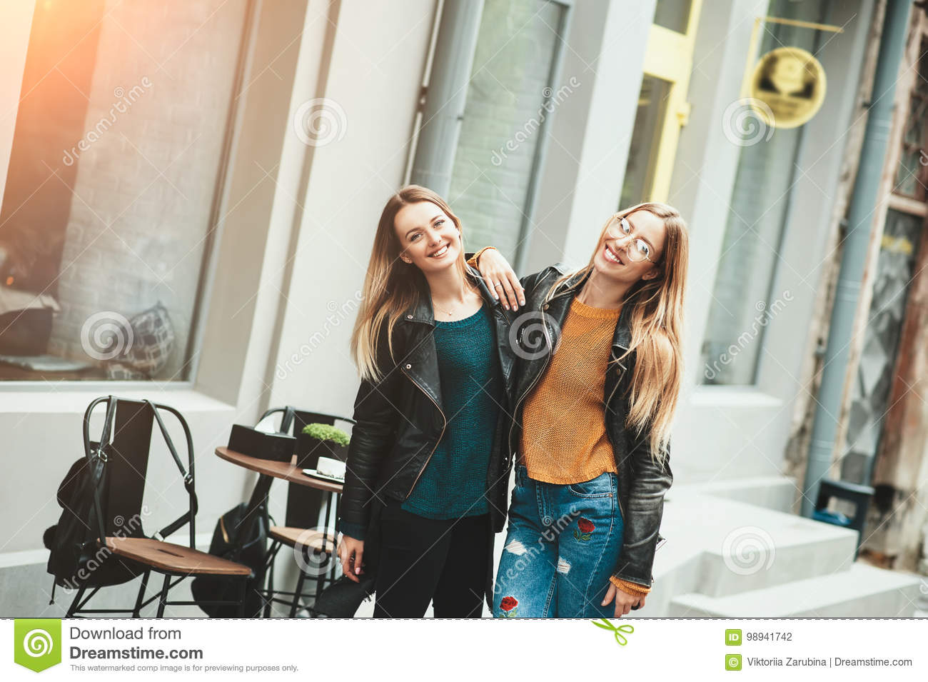 It is funny walk with best friend! Two beautiful women walking outdoor hugging and laughing on autumn street.
