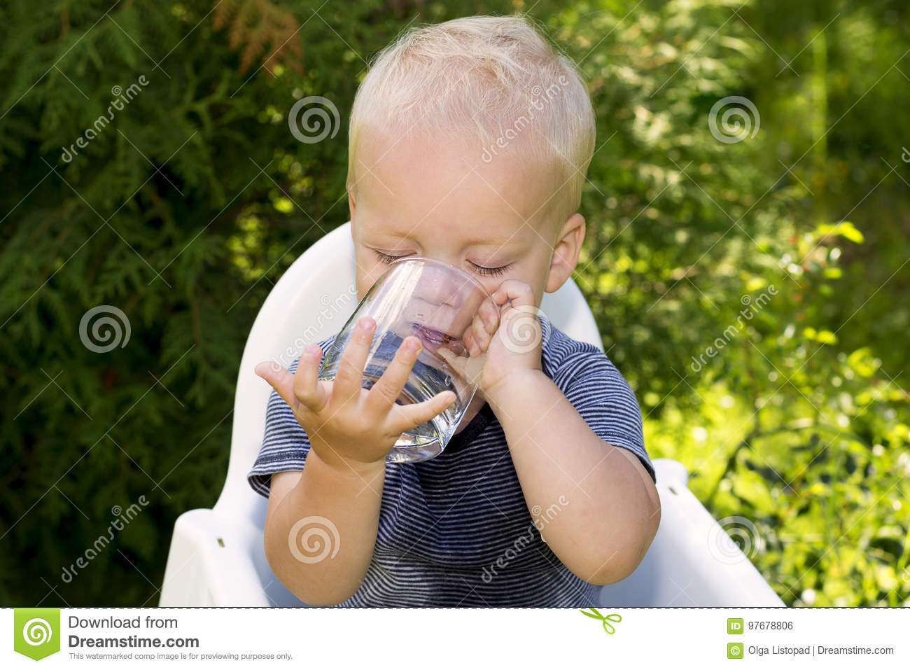 Funny wet baby boy trying to drink water from the glass independently