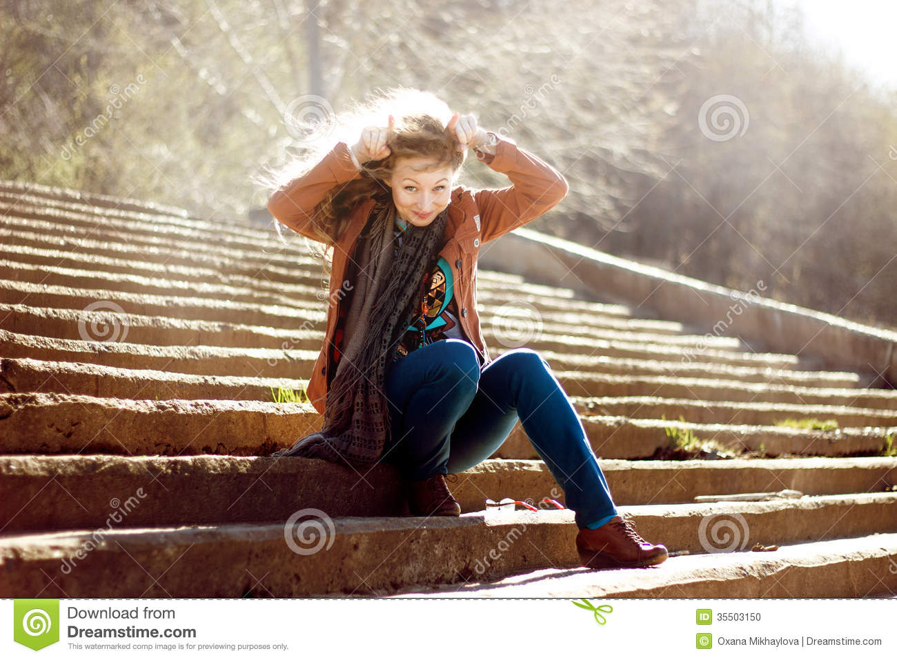 funny woman with blonde curly hair on stairs background