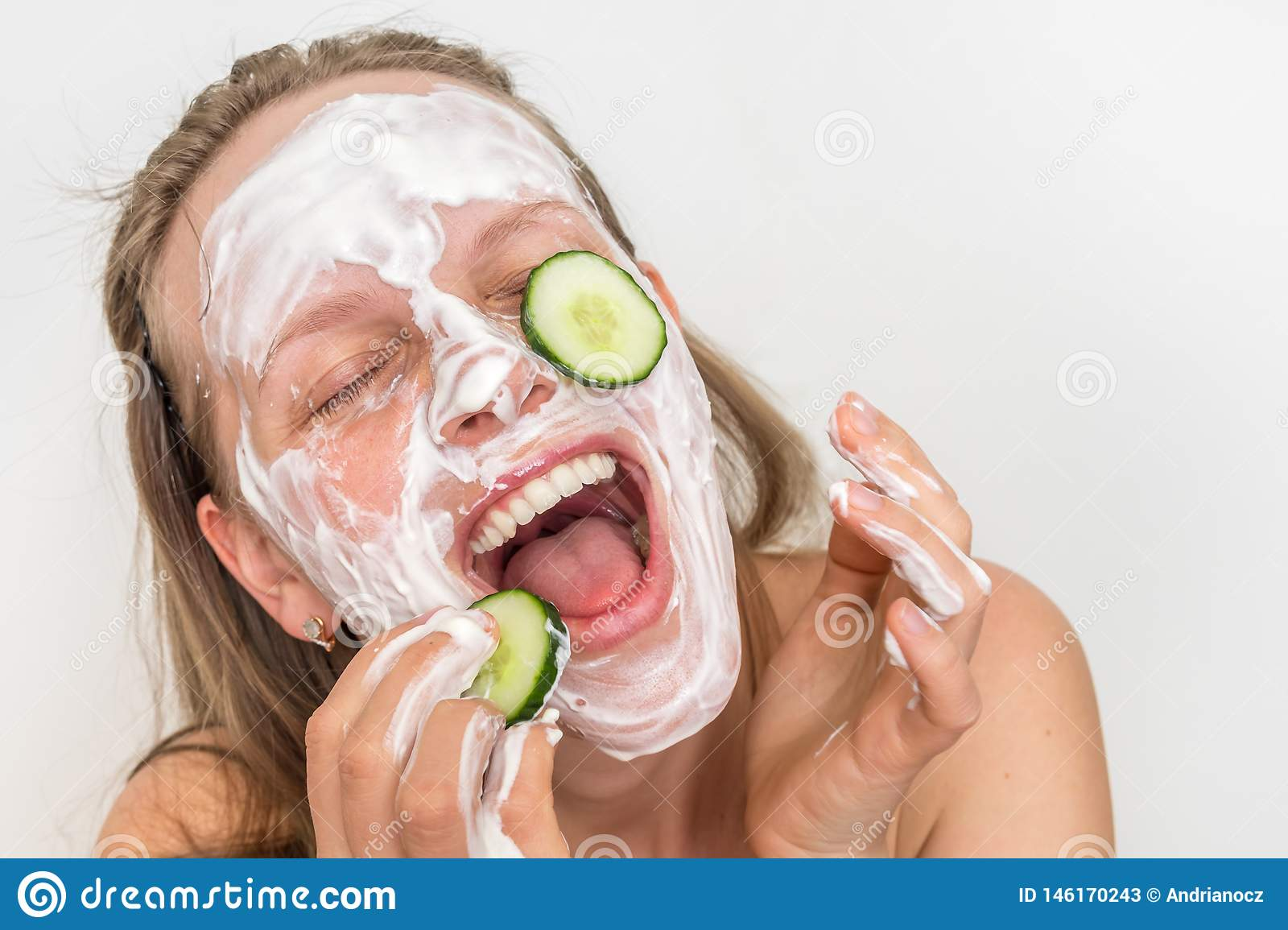 Woman with natural cream mask and cucumbers on her face