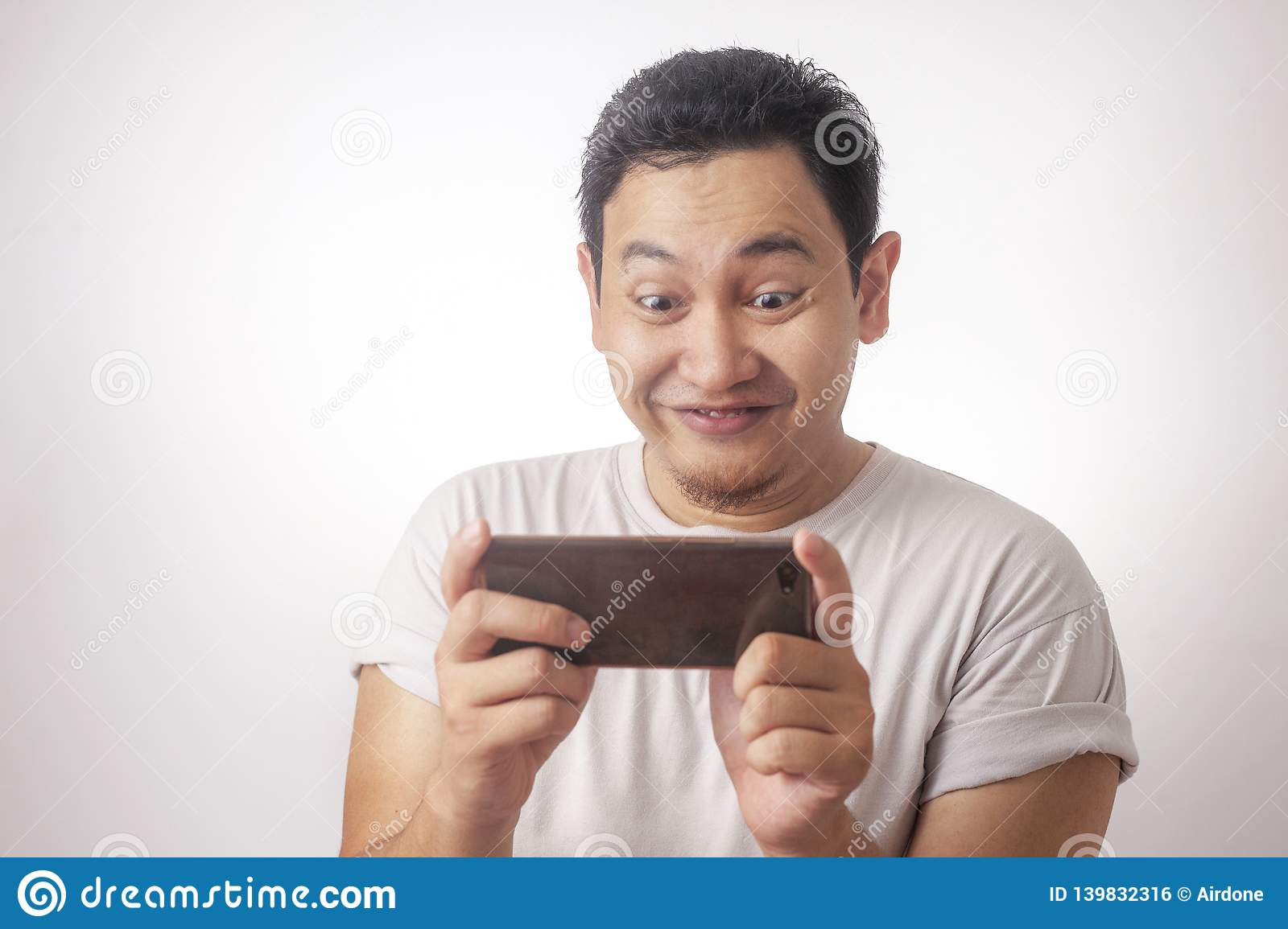 Funny Young Asian Guy Playing Games on Tablet Smart Phone