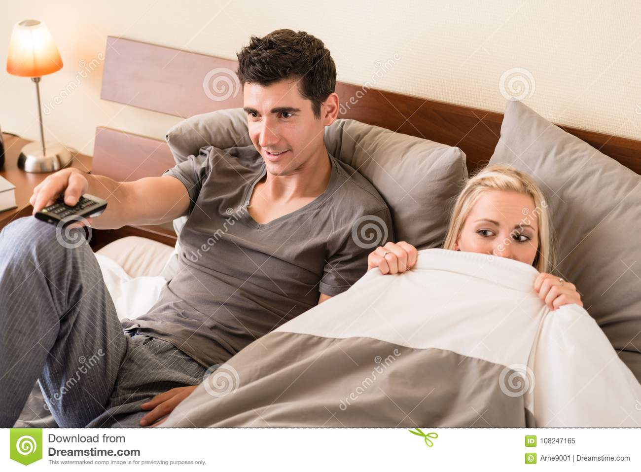 Couple sitting in bed while watching TV