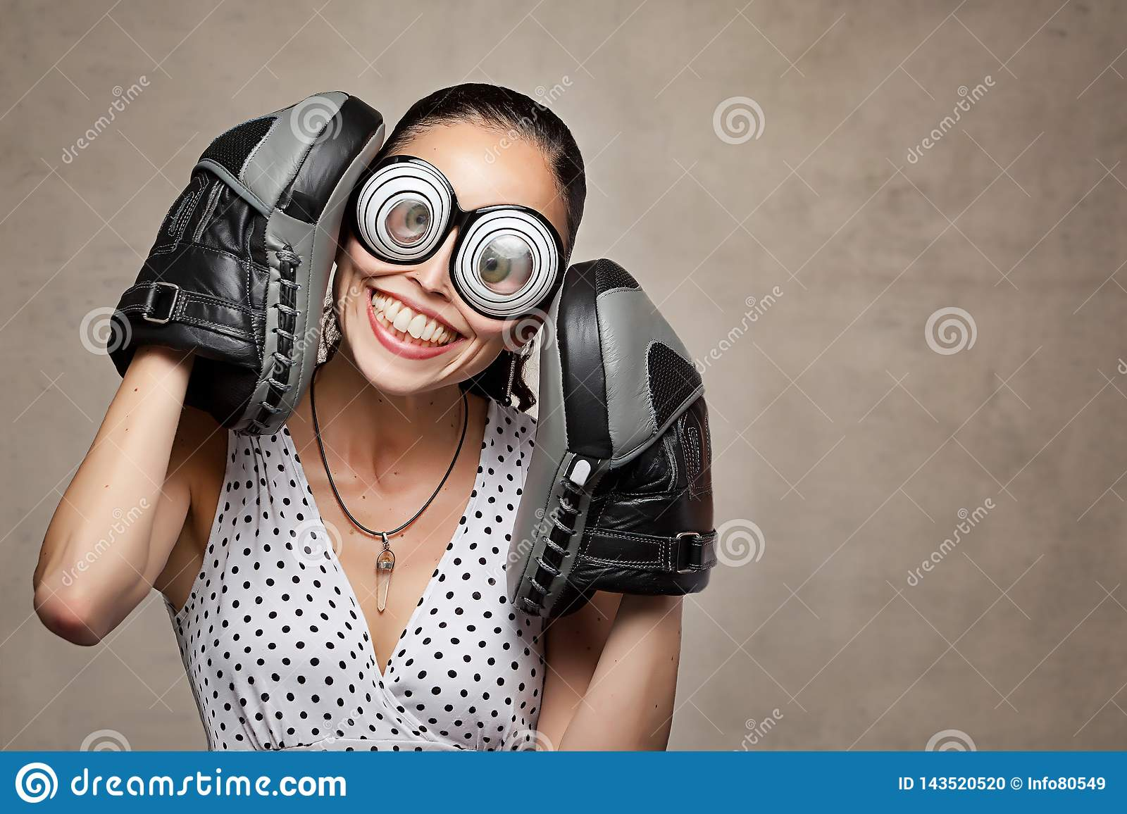 Funny crazy woman with big eyes, glasses and boxing gloves