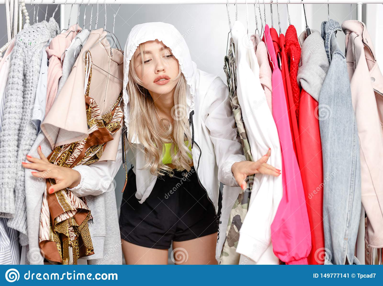 Funny young girl blogger dressed in fashionable clothes standing between clothes hanging on a hanger in the wardrobe
