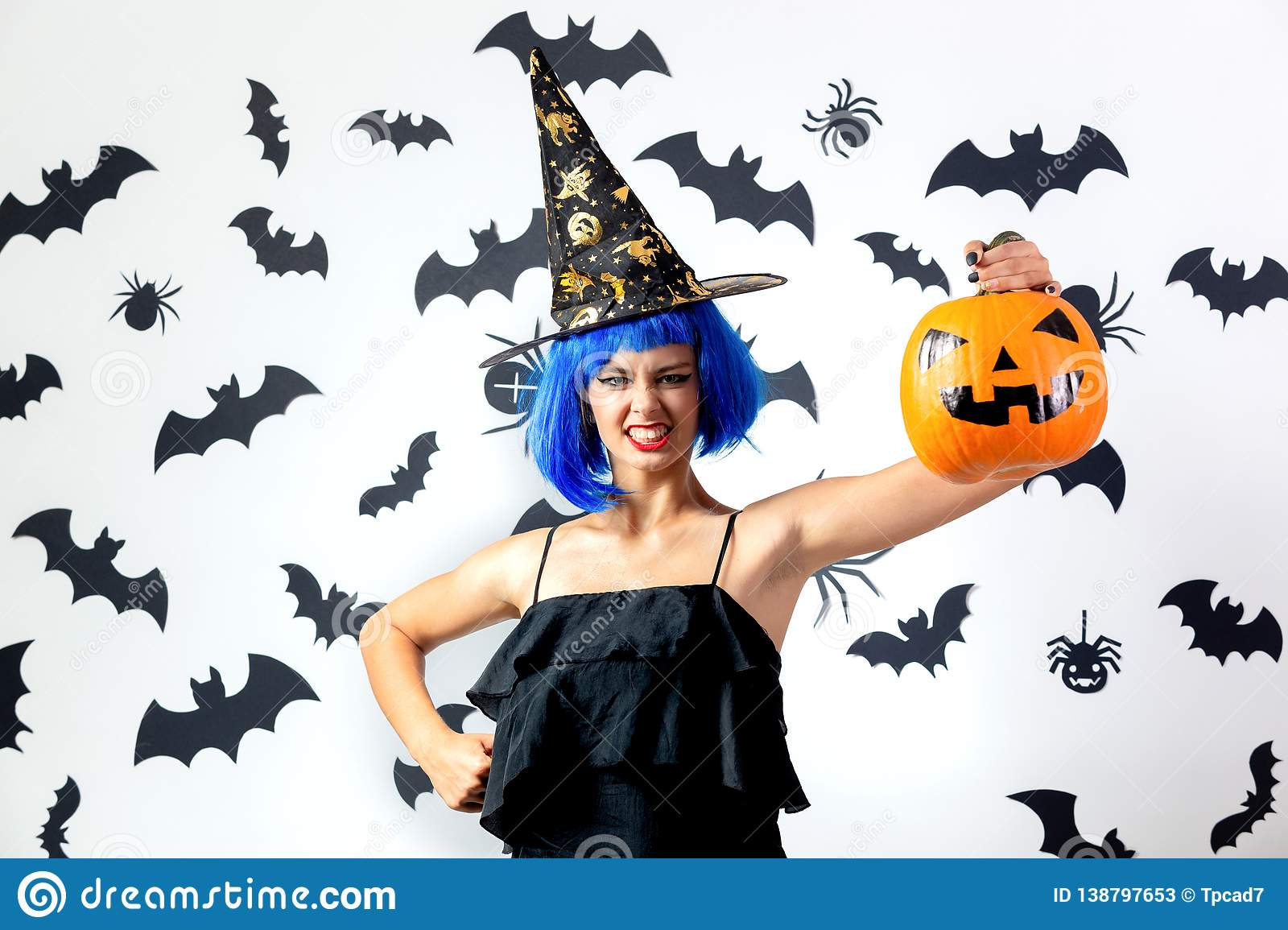 Funny young woman in a blue wig and witch`s hat holds Halloween pumpkin on a white background with black bats and