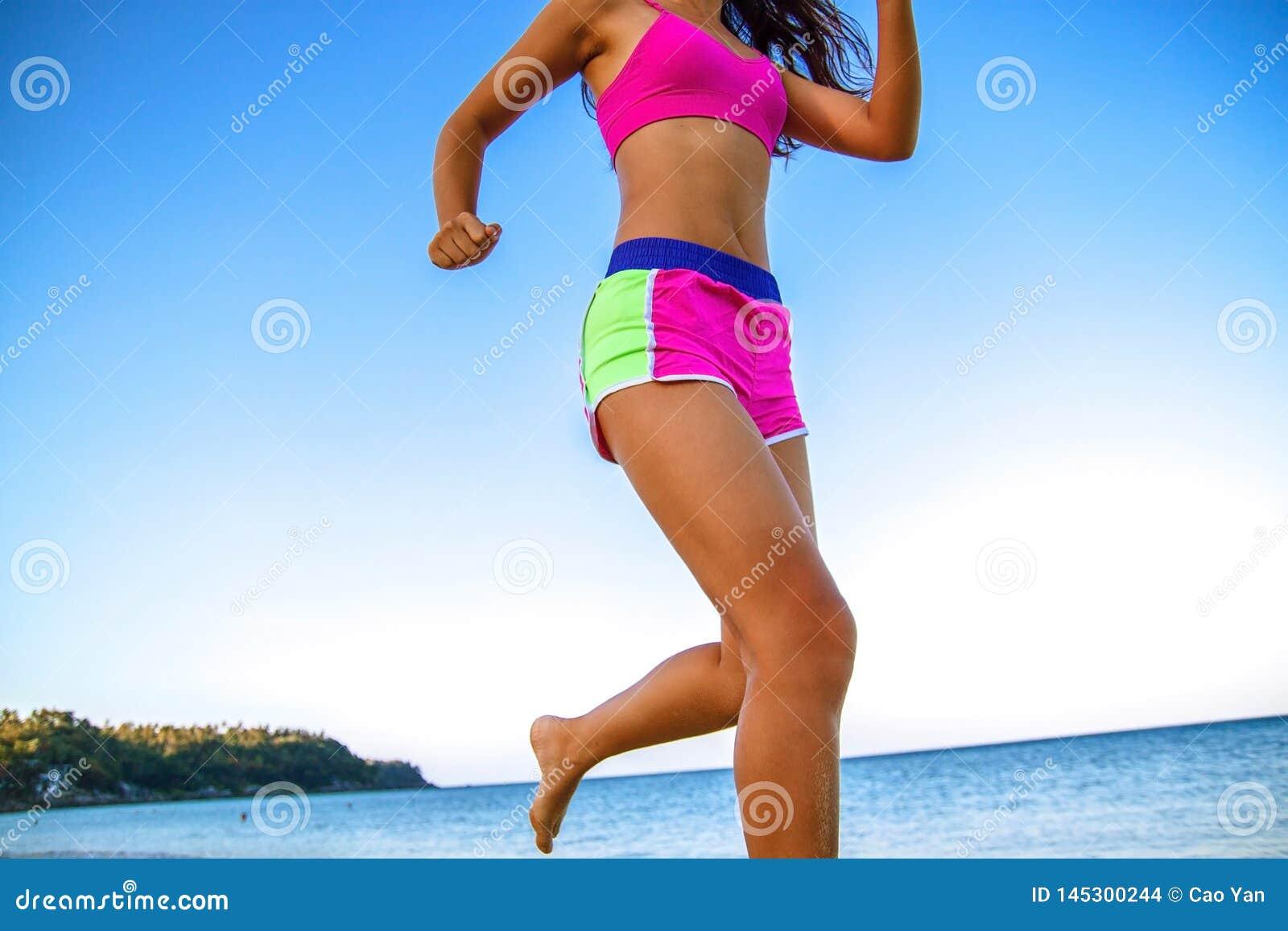 Funzionamento atletico della donna di forma fisica sulla spiaggia Allenamento esterno