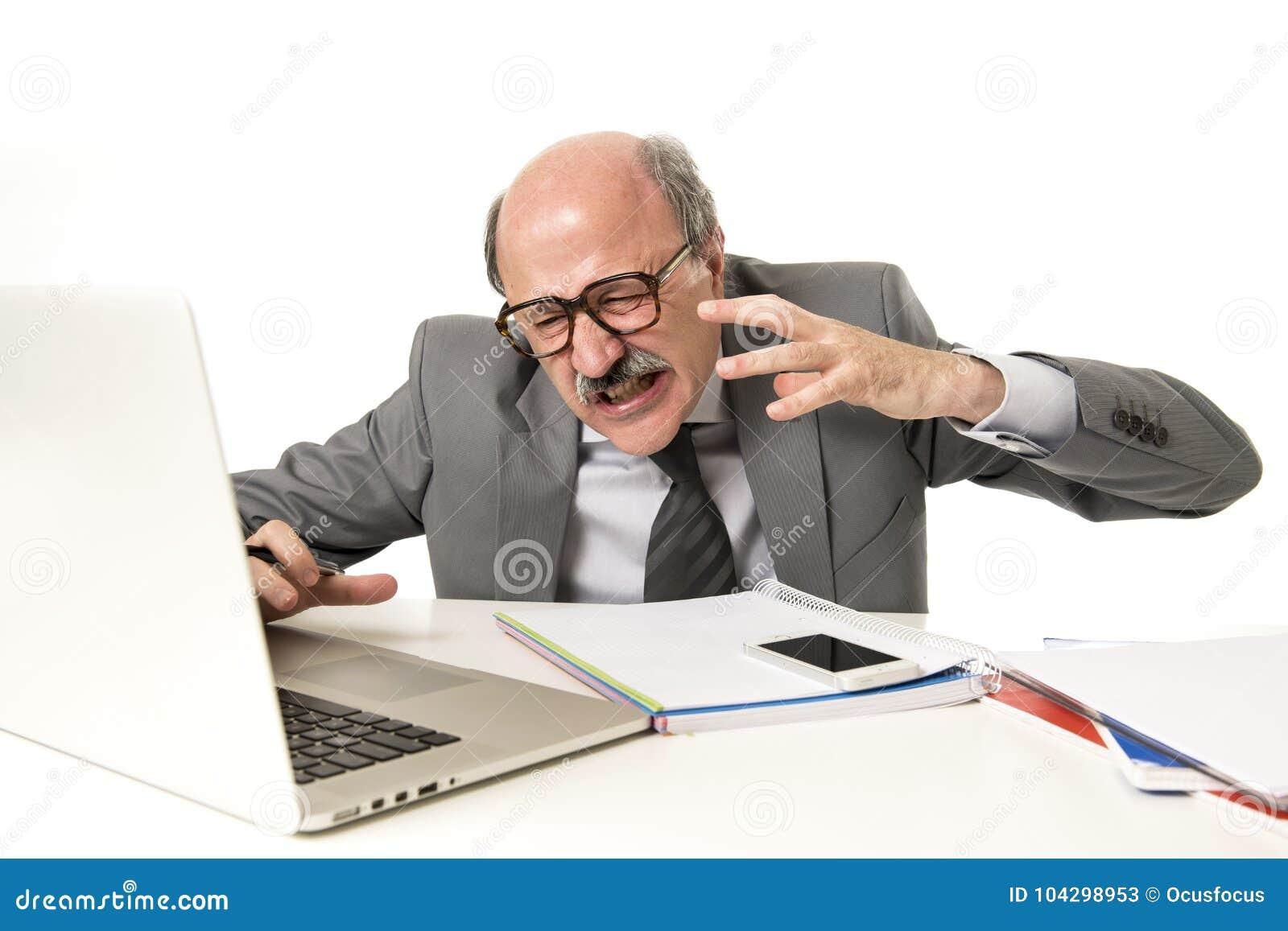 Funzionamento calvo dell uomo 60s di affari sollecitato e frustrato allo scrittorio del computer portatile del computer di uffici