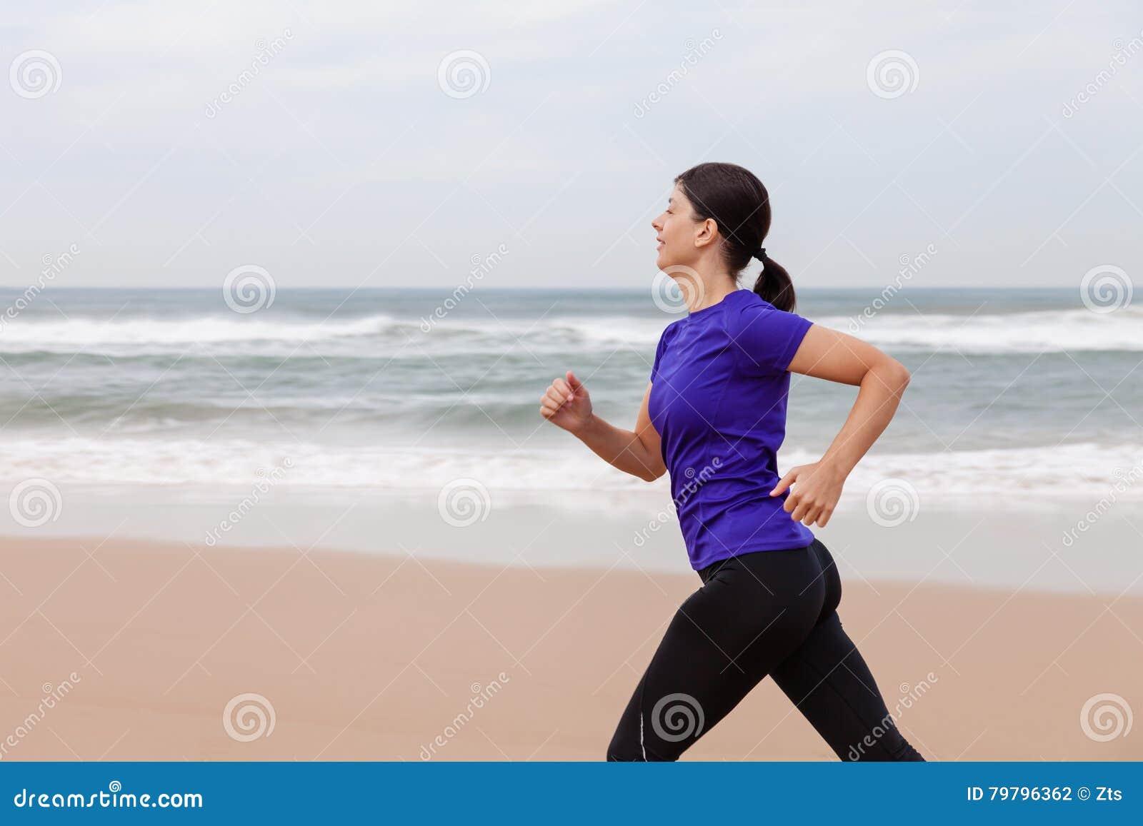 Funzionamento dell atleta femminile alla spiaggia un giorno dell autunno