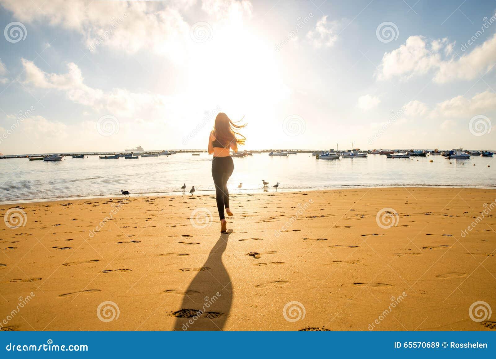 Funzionamento della donna sulla spiaggia sabbiosa