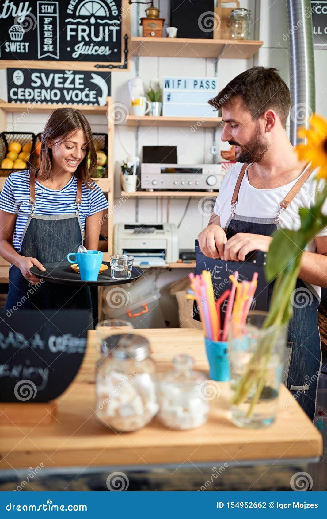 Funzionamento di barista della donna in caffetteria e tazza servente di caffè fresco