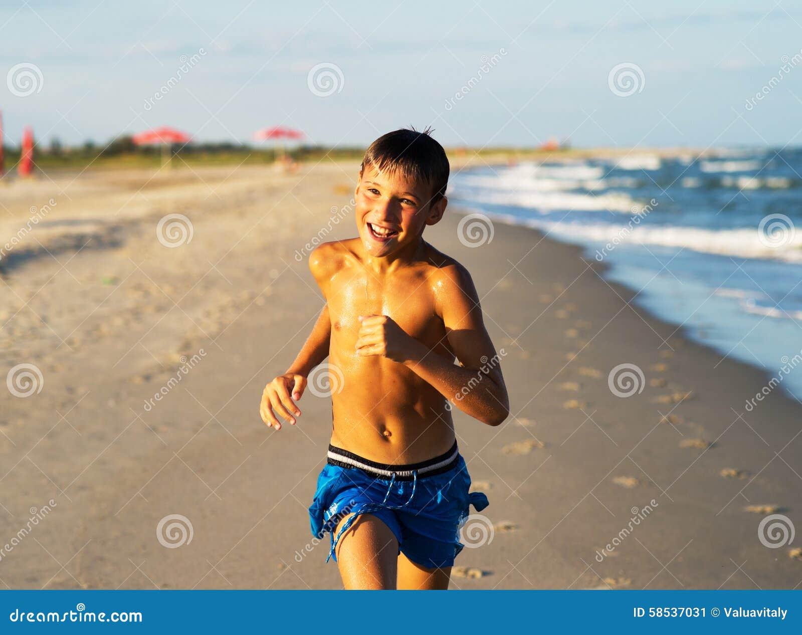 Funzionamento felice del ragazzo sulla spiaggia del mare ad estate