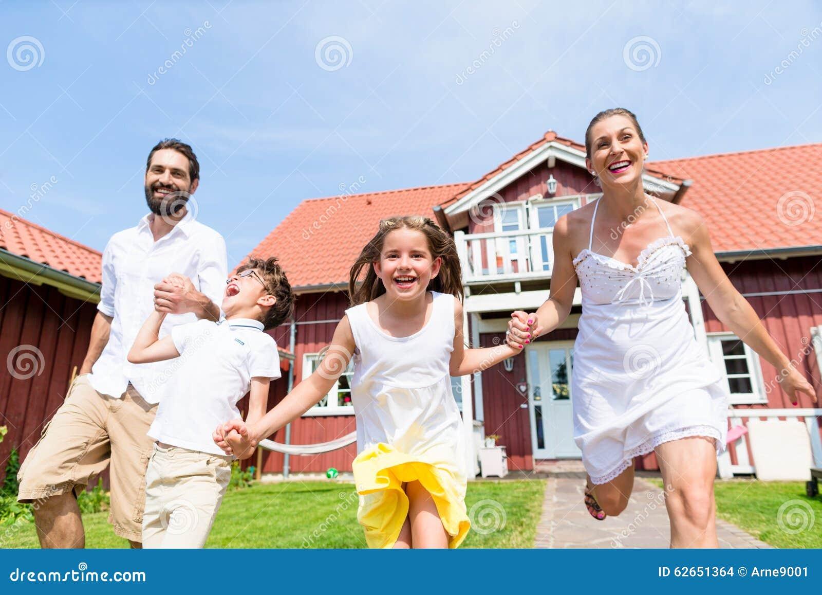 Funzionamento felice della famiglia sul prato davanti alla for Ponte sul davanti della casa