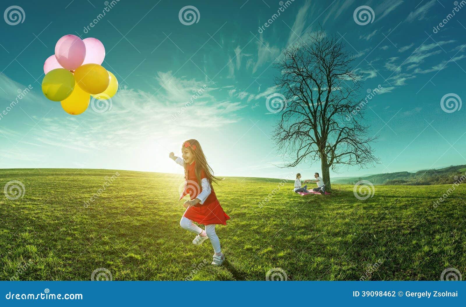 Funzionamento felice della ragazza in un prato con i palloni