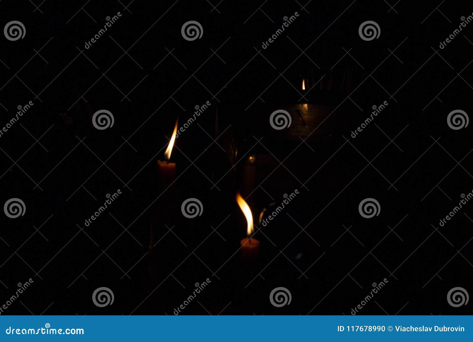 La Credenza Religiosa : Fuoco arancio delle candele nelloscurità il rituale religioso della