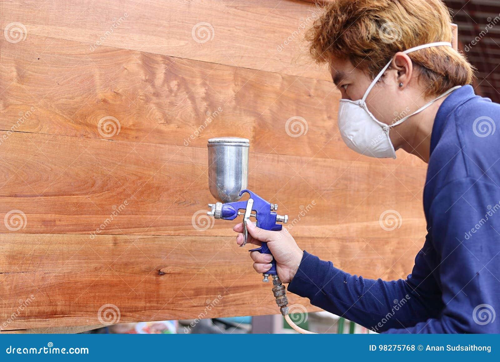 Fuoco selettivo sulle mani di giovane lavoratore asiatico con la maschera di sicurezza che dipinge un pezzo di legno con la pisto