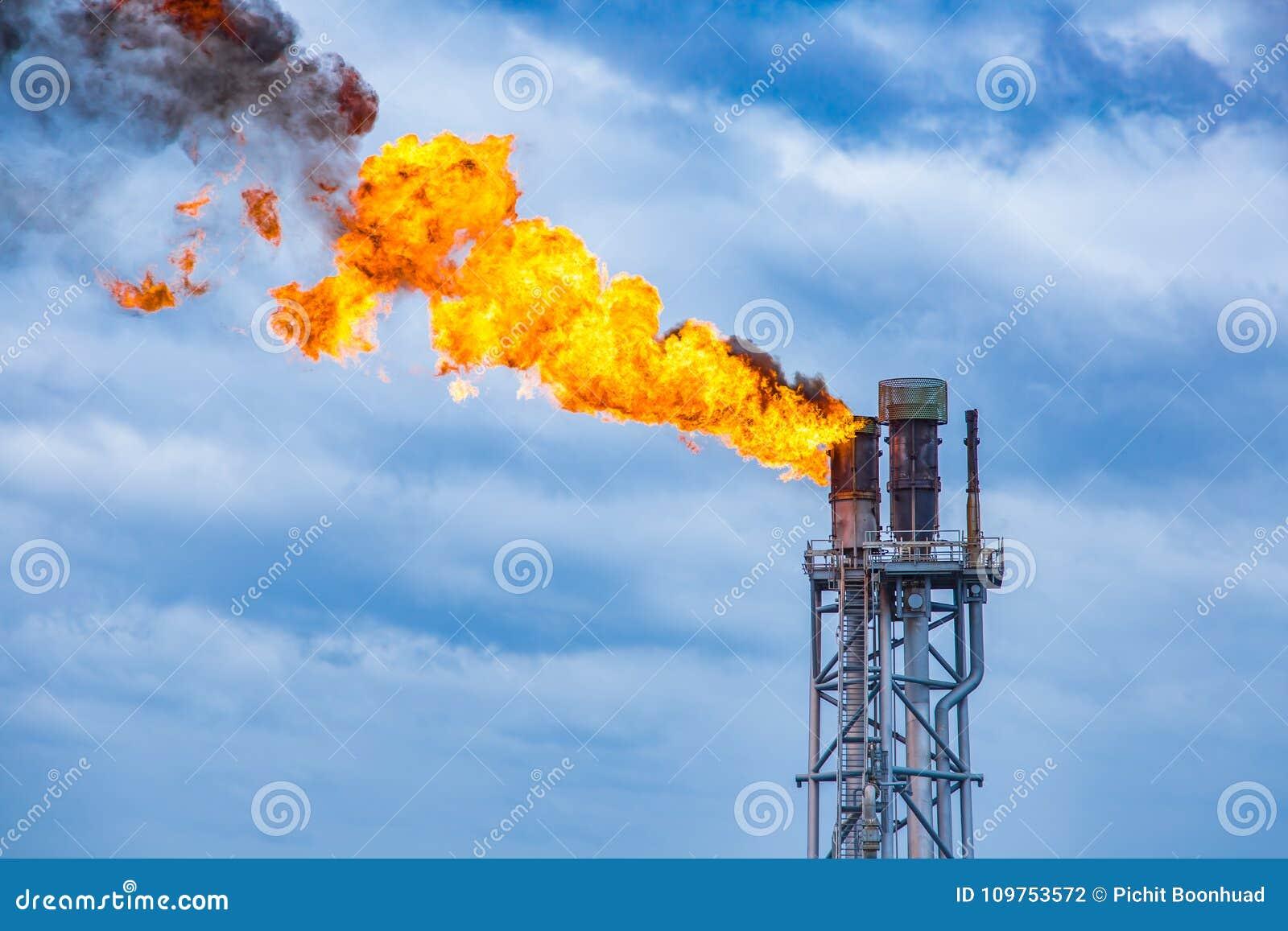 Fuoco sulla fiaccola alla piattaforma d elaborazione centrale del gas e del petrolio mentre bruciando sostanza tossica e rilascio
