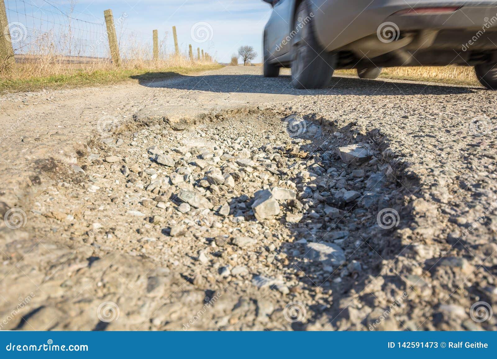 Furo perigoso na superfície do asfalto de uma estrada com passagem do carro