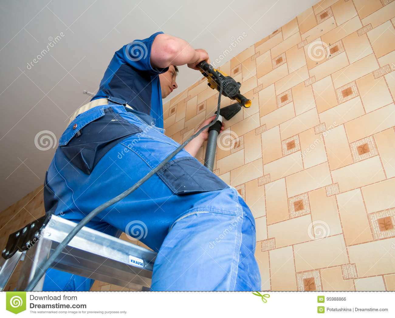 Furos de brocas do trabalhador na parede com um perfurador
