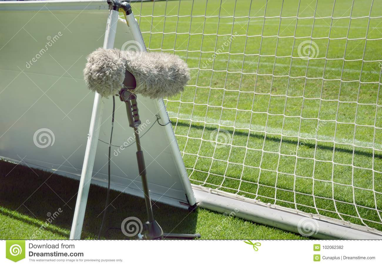 472600ca8 Furry sport microphone on a soccer field behind the goal net in sunny day