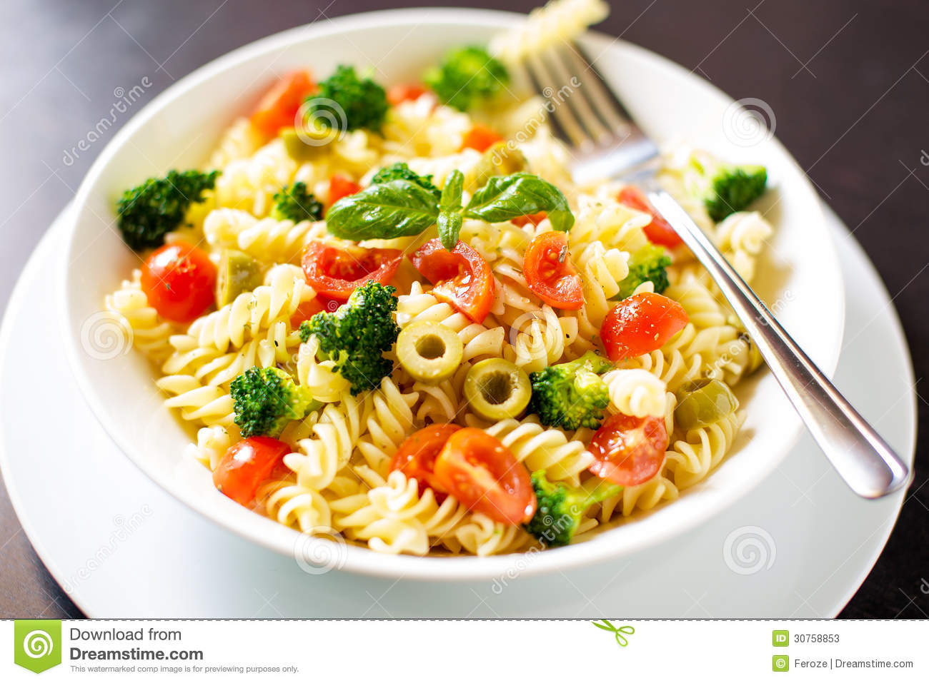 Fusilli pasta with broccoli, tomatoes, olives and basil.