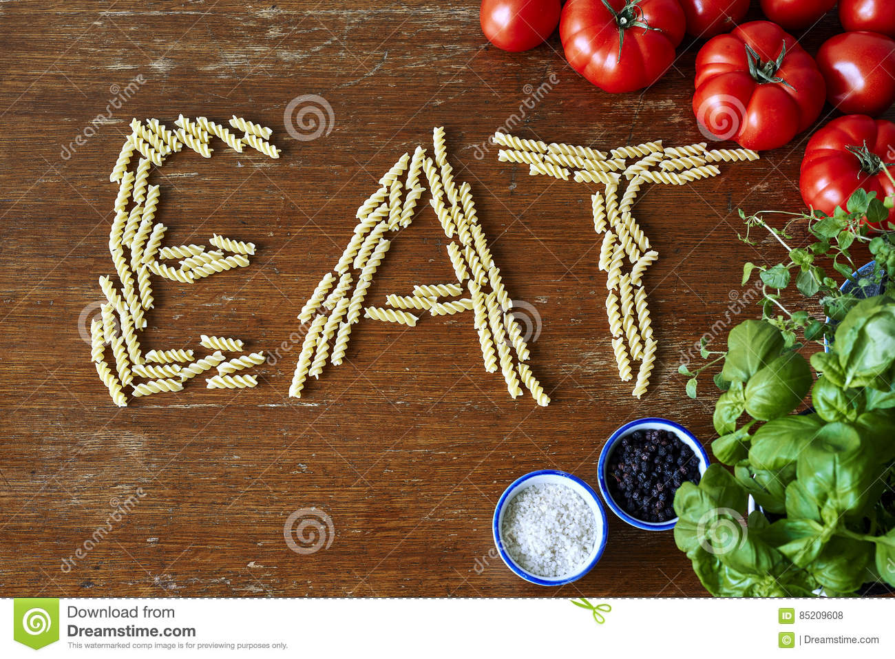 Fusilli Pasta Tomatoes And Herbs Forming The Word Eat Stock Photo