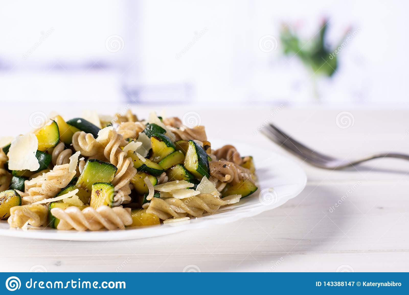 Fusilli pasta with zucchini with red tulips