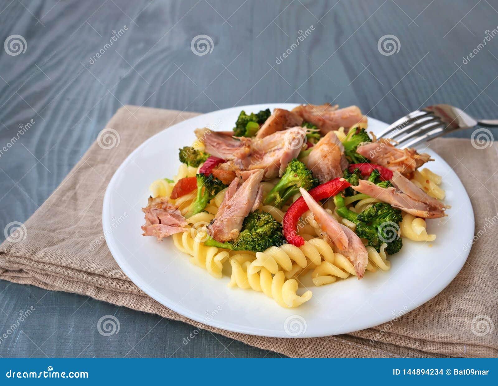 Fusillideegwaren met getrokken kippenvlees, broccoli en groenten op witte plaat