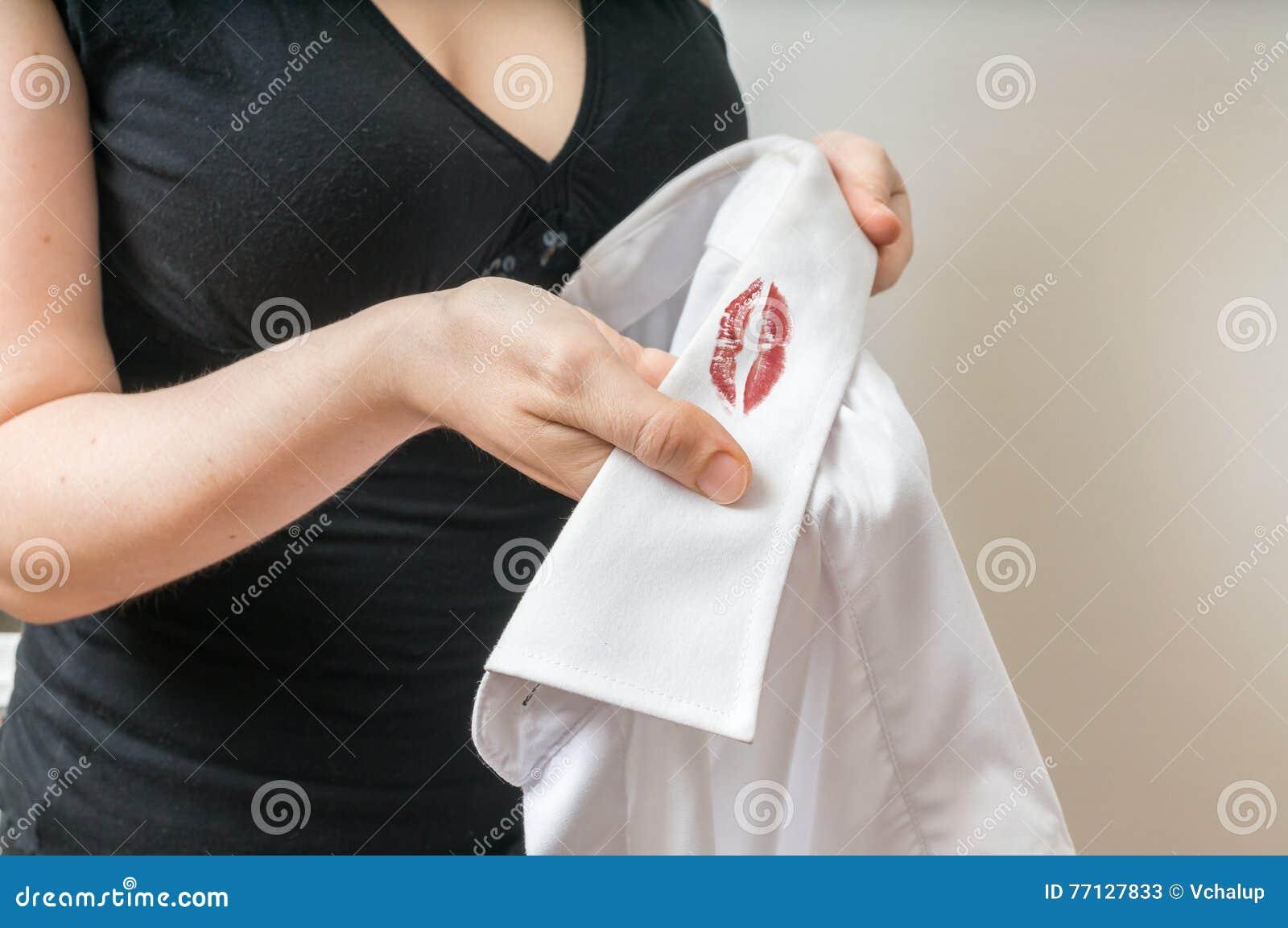 Fusk- och äktenskaplig otrohetbegrepp Kvinnan rymmer den vita skjortan av hennes make med röda läppstiftfläckar