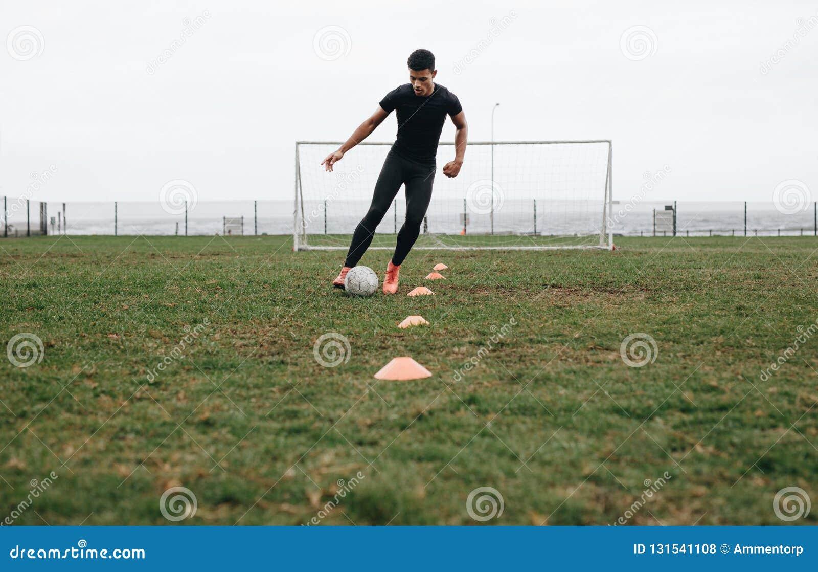 Futbolista robi rożkowi drybluje świder na polu Futbolista rusza się piłkę między rożkami ćwiczy dryblować