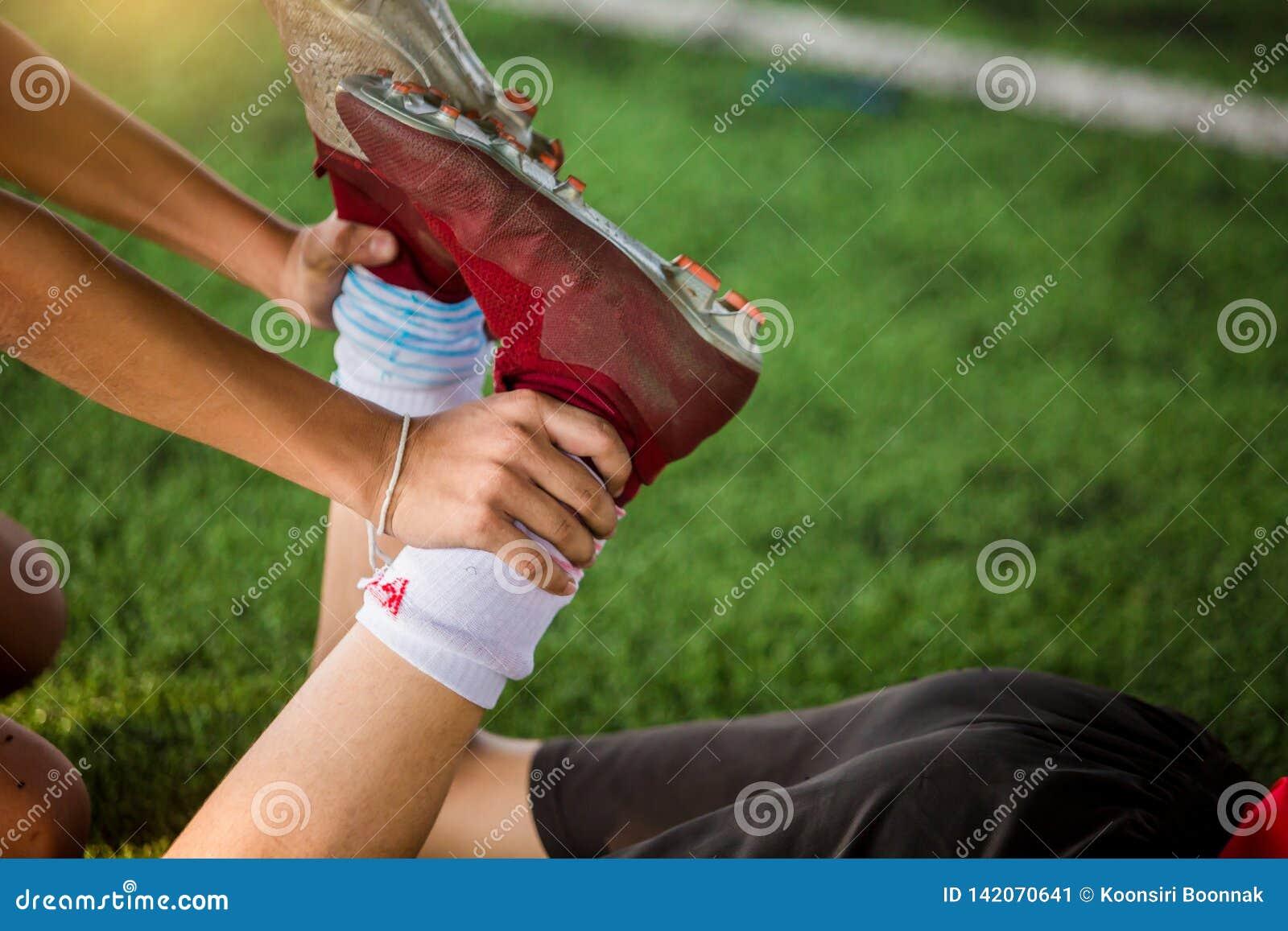 Futbolista trzyma kostkę rozciągać mięśnie