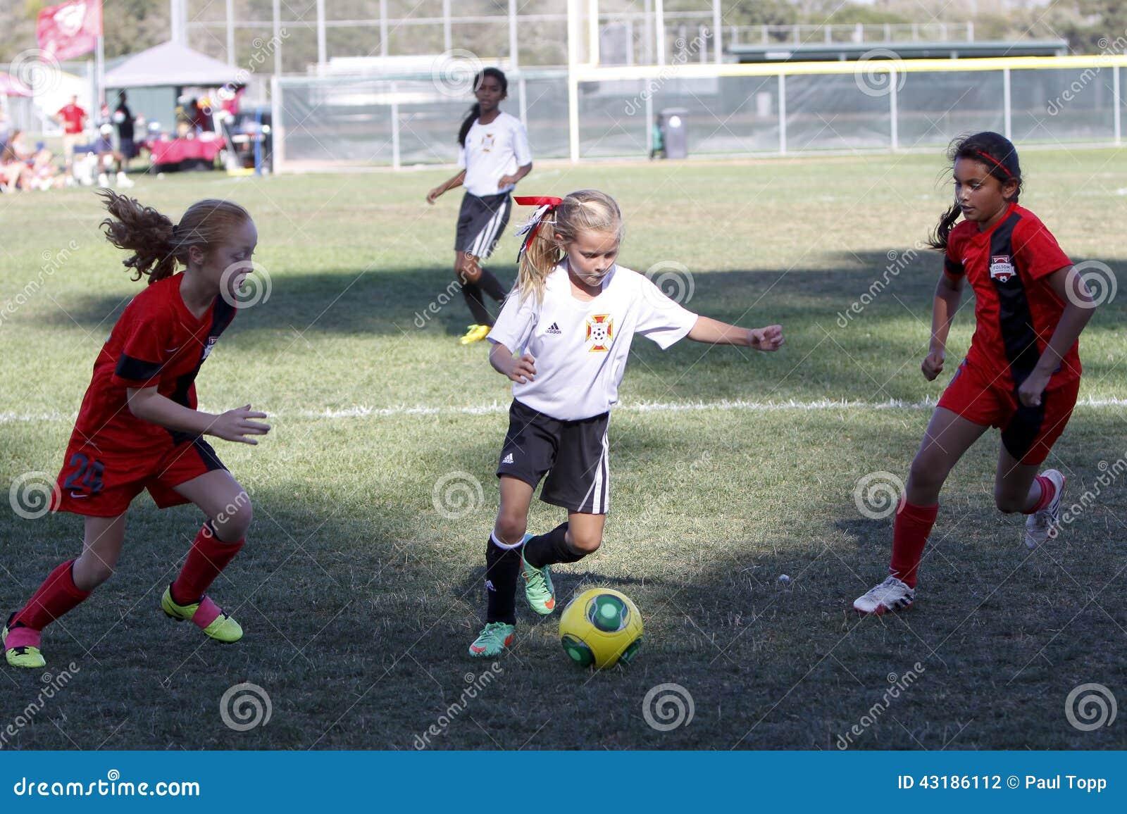 Futbolistas del fútbol de la juventud de las muchachas que corren para la bola