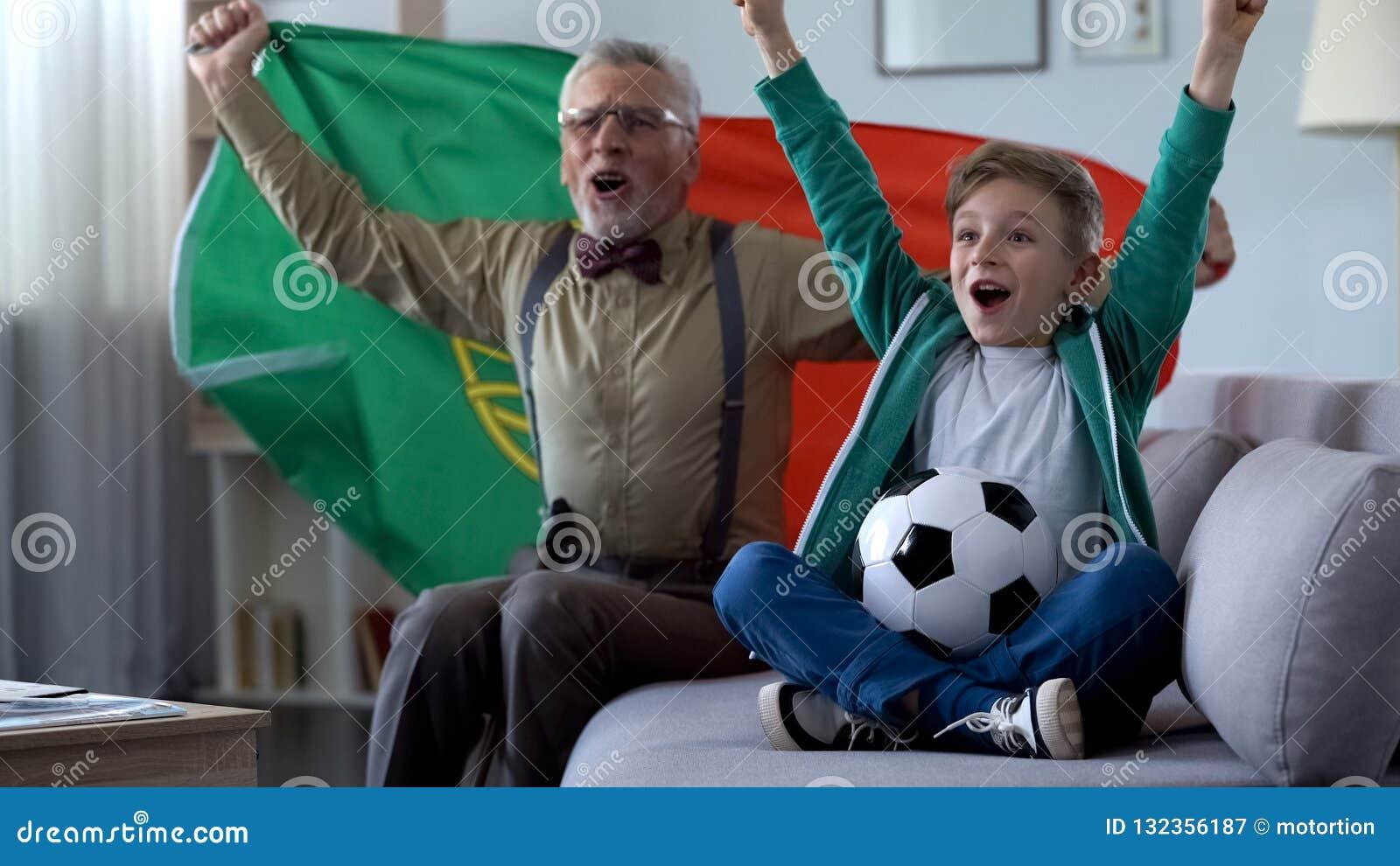 Futebol de observação do vovô e do neto, bandeira portuguesa de ondulação, feliz para a vitória