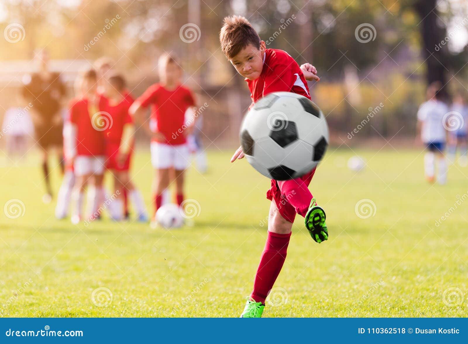 Futebol de retrocesso do menino no campo de esportes