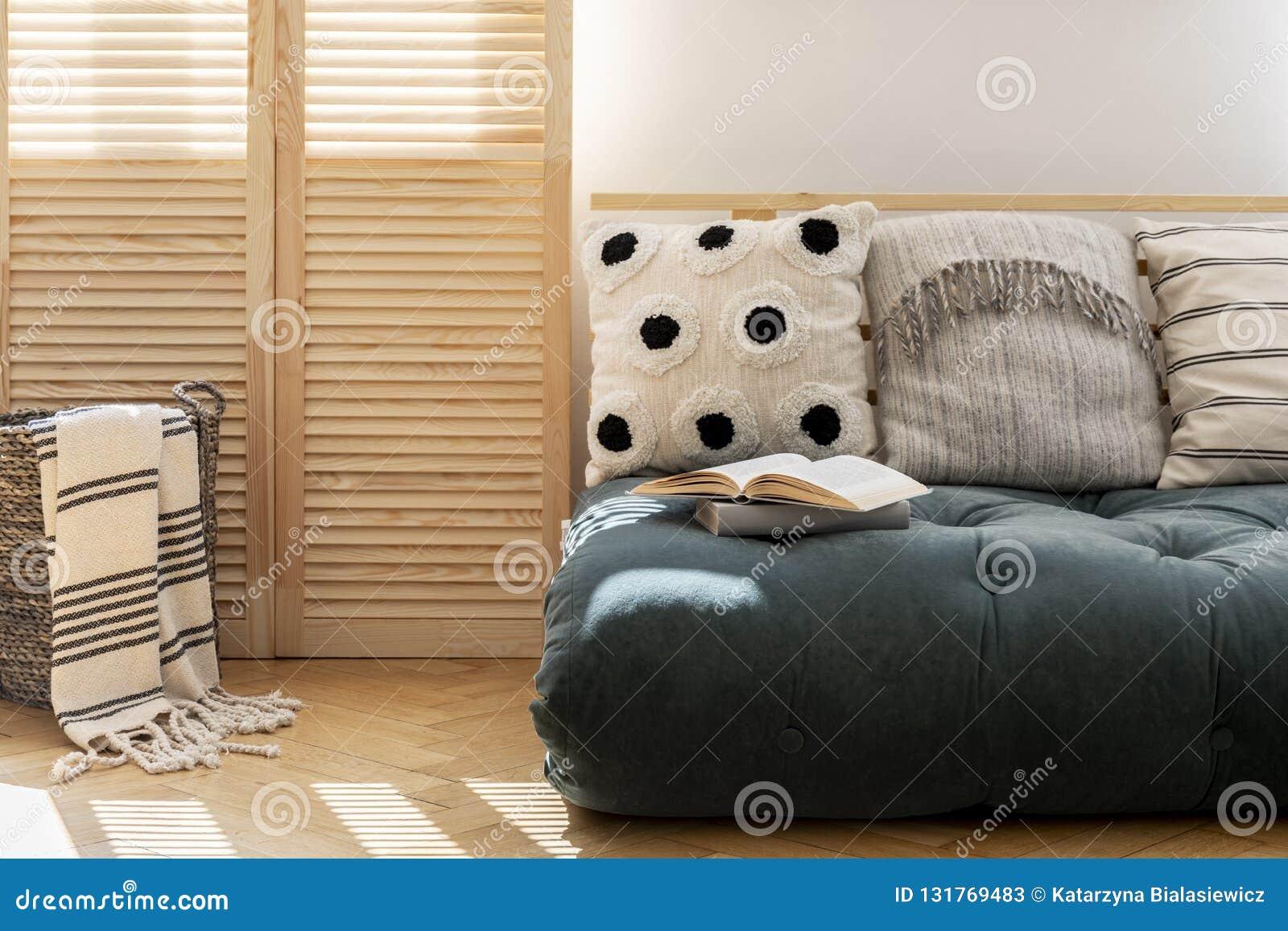 Futon escandinavo con las almohadas en interior espacioso de la sala de estar del apartamento moderno