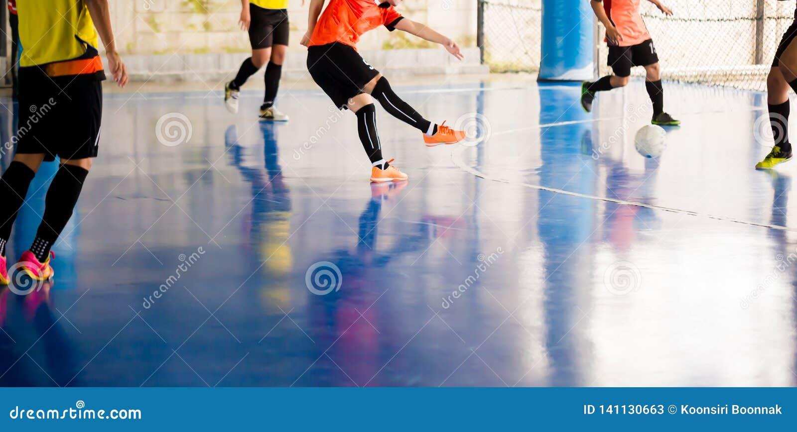 Futsal spelarefälla och att kontrollera bollen för fors till målet Fotbollspelare som slåss sig, genom att sparka bollen Inomhus