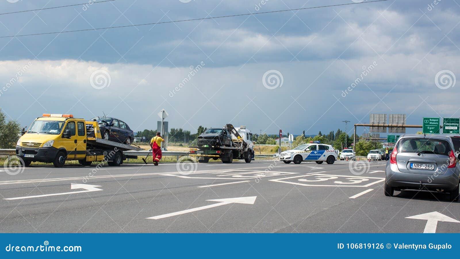 Fuzesabony, Węgry Dwa samochodu są na holowniczych ciężarówkach po wypadku na drodze Policja blokująca kupczy potłuczone szkło