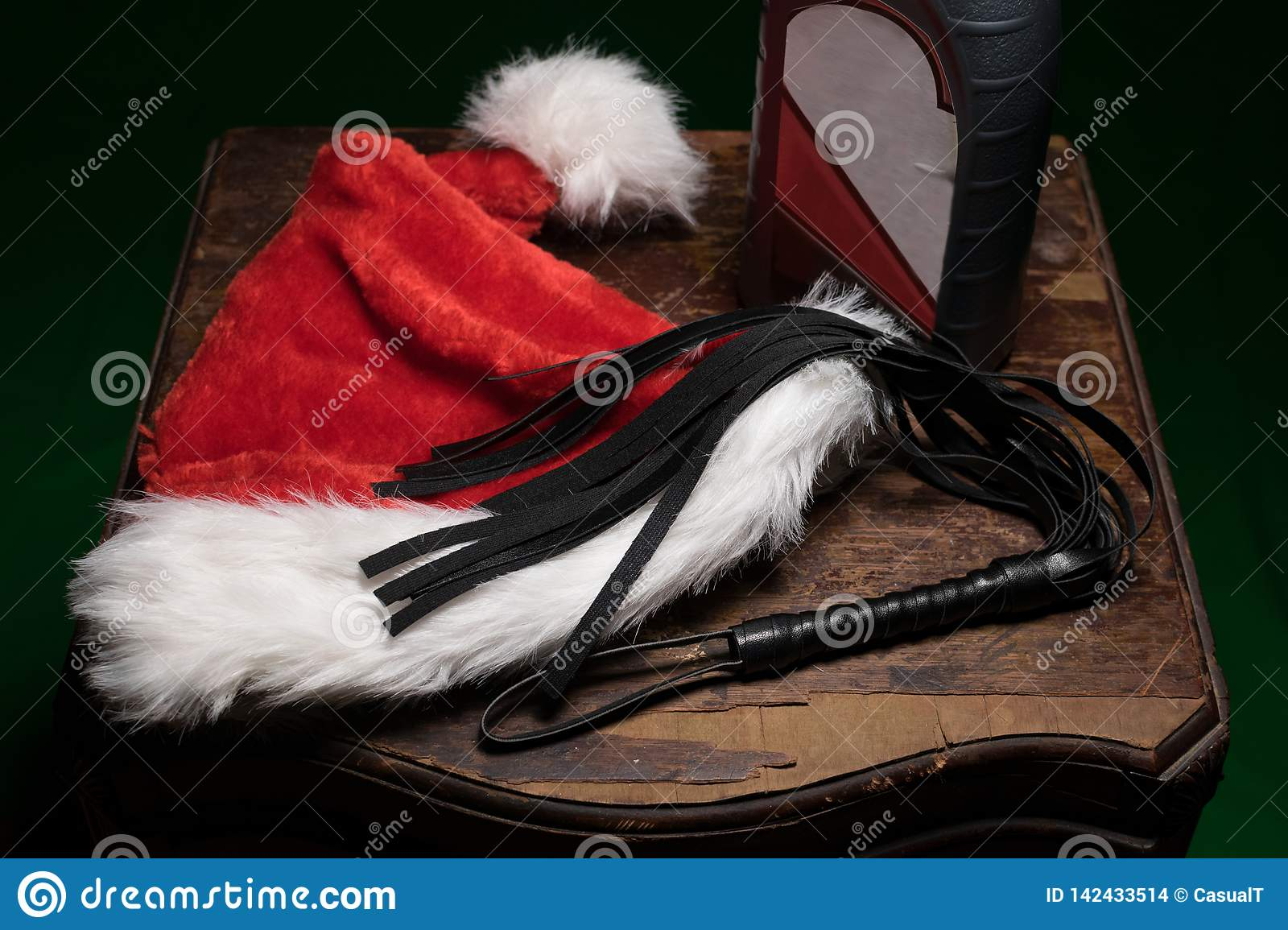 A fuzzy red and white Santa hat, a black whip, and a bottle of motor oil, on an old wodden table, spreading a special kind of