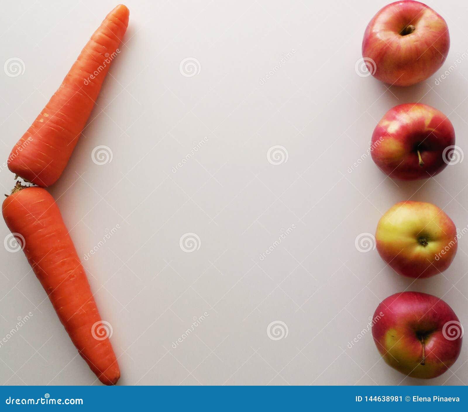 Fyra äpplen och två morötter på en vit bakgrund