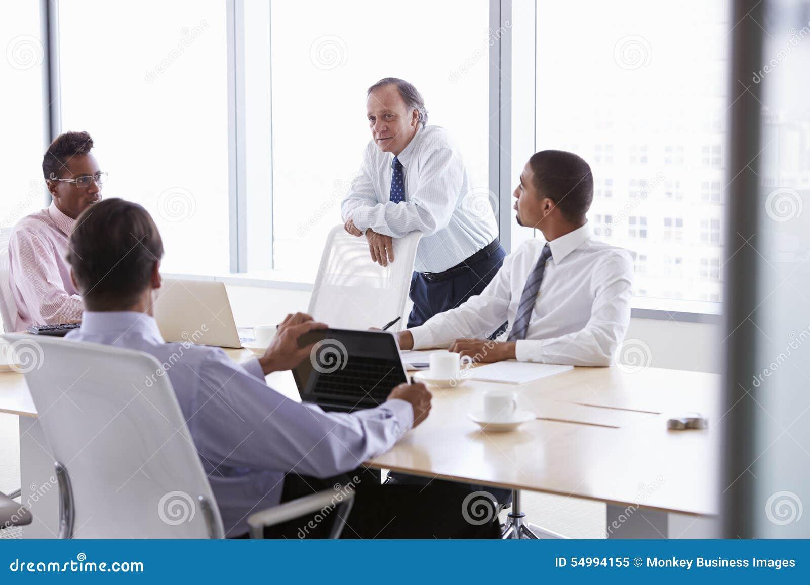 Fyra affärsmän som har möte runt om styrelsetabellen