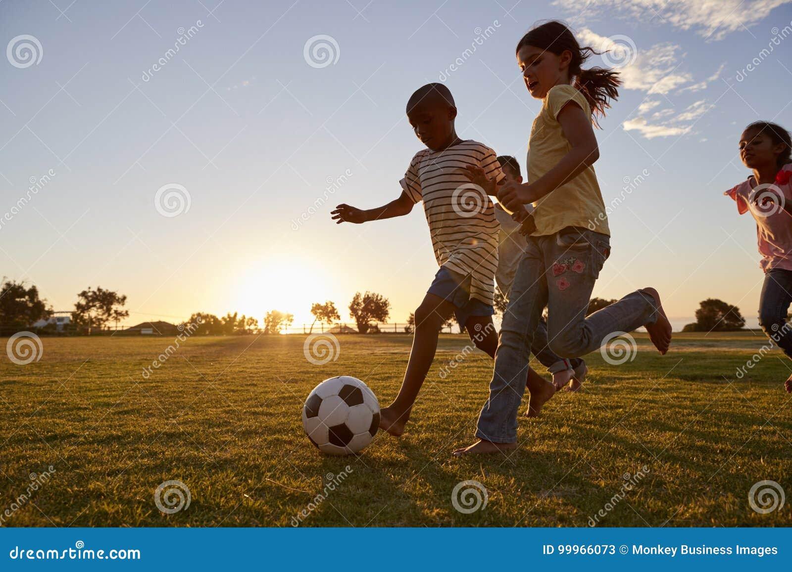 Fyra barn som springer efter en fotboll som plying på ett fält
