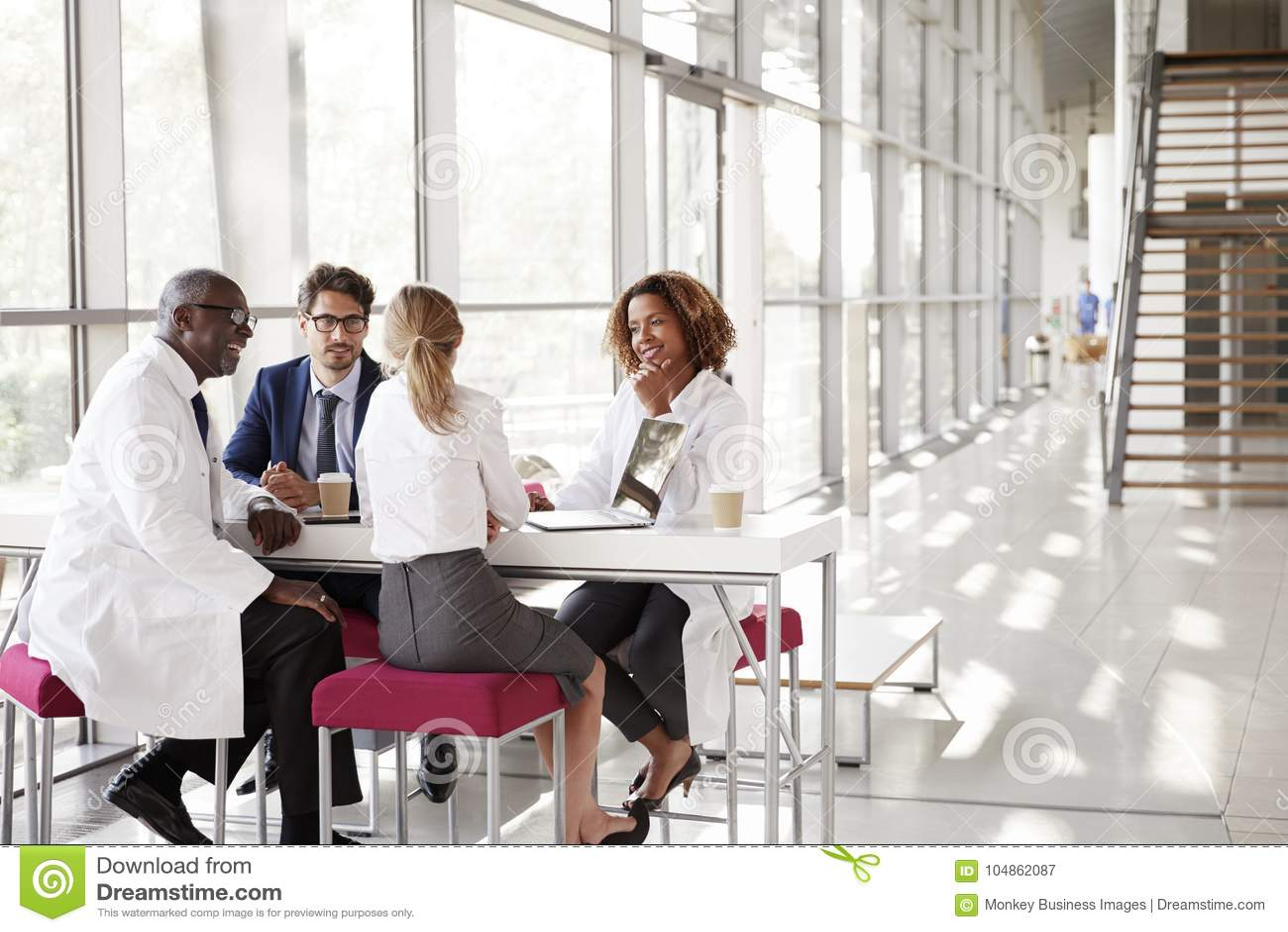 Fyra doktorer som talar på en tabell i ett modernt sjukhus, övar påtryckningar