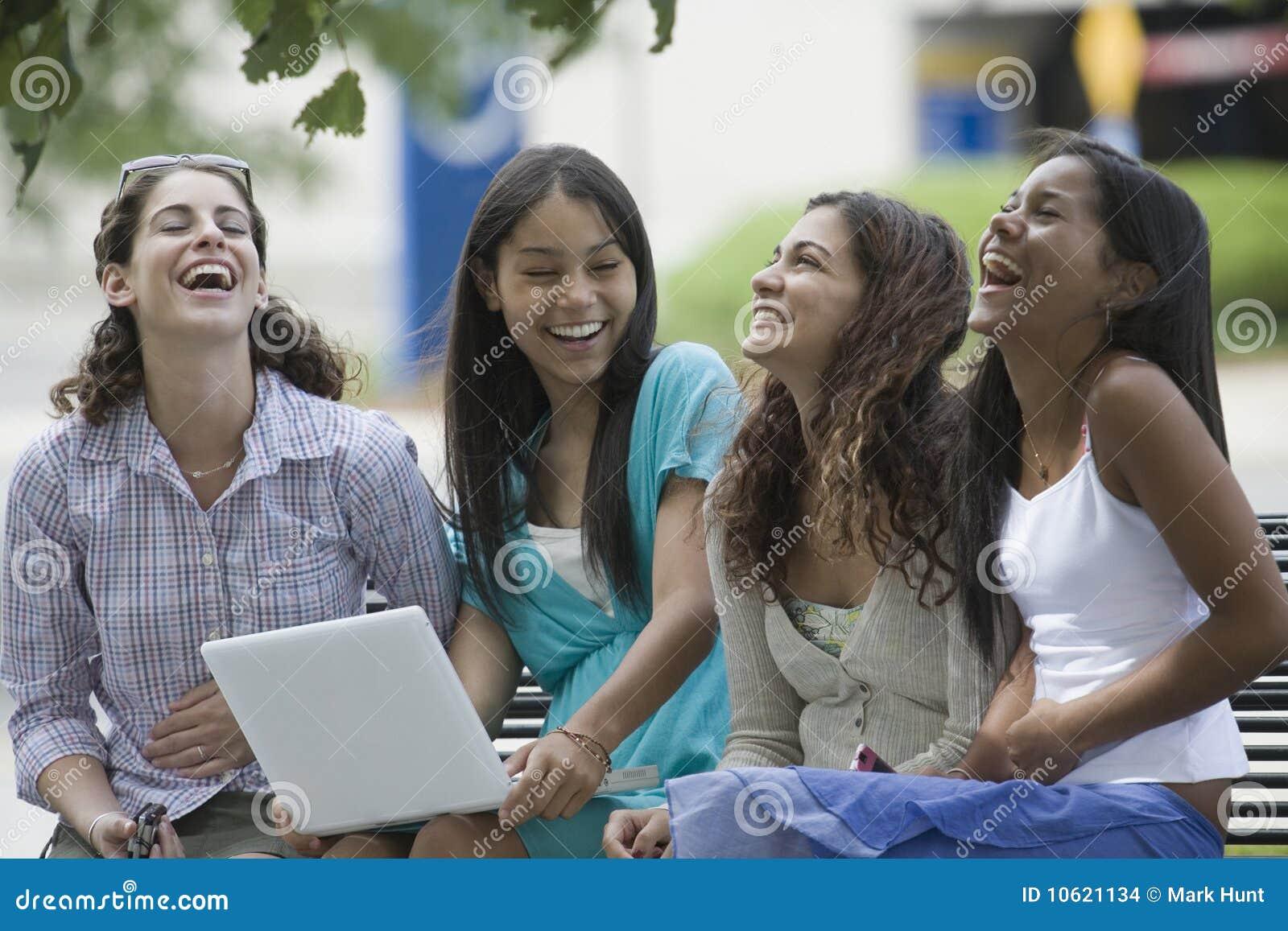 Fyra flickor som sitter att le som är tonårs-