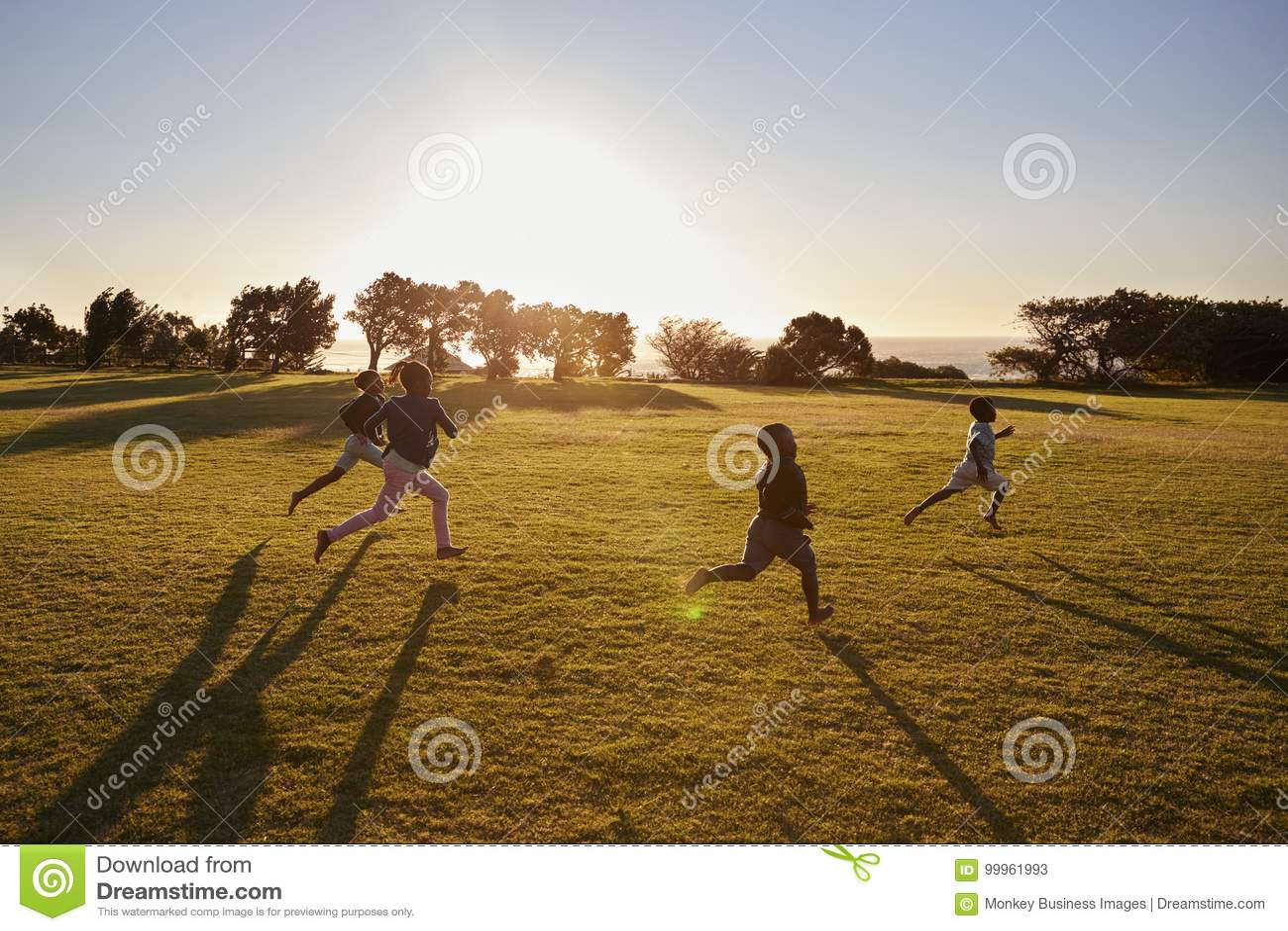 Fyra grundskolabarn som kör i ett öppet fält