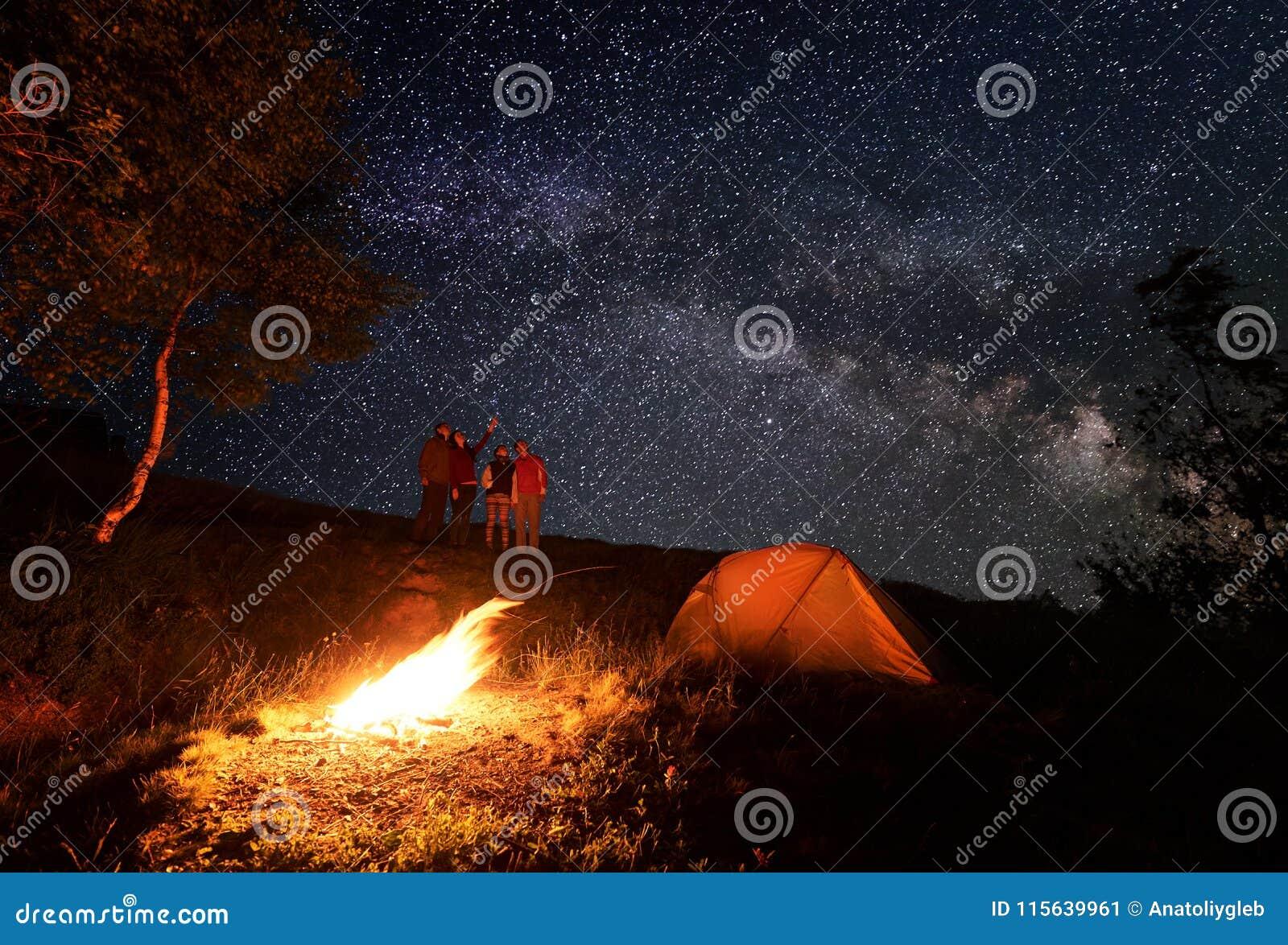 Fyra - personen tycker om den ovanliga himlen som beströs med ljusa stjärnor under campa för natt