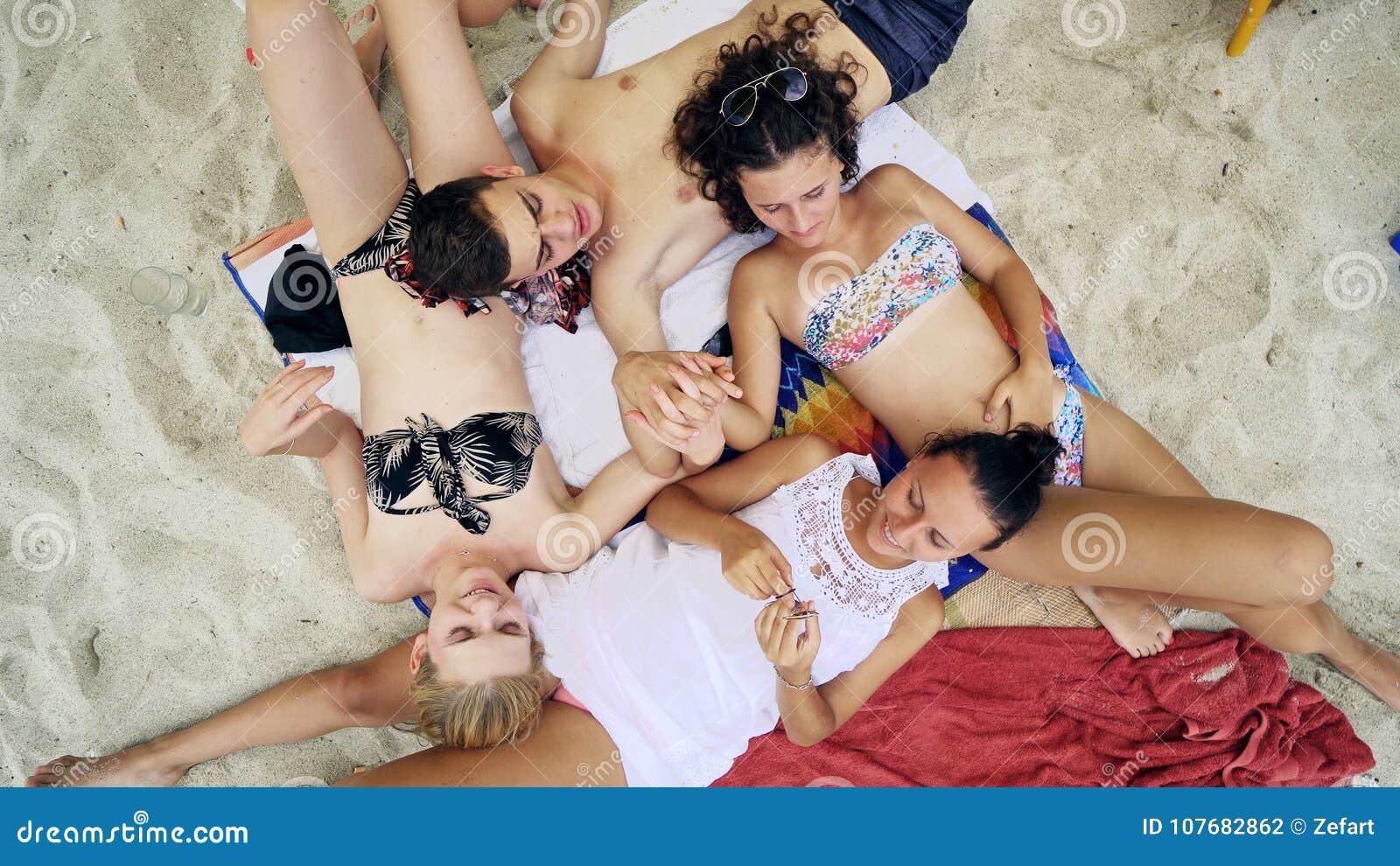 Fyra tonårs- vänner som ligger på den sandiga stranden och rymmer vid händer