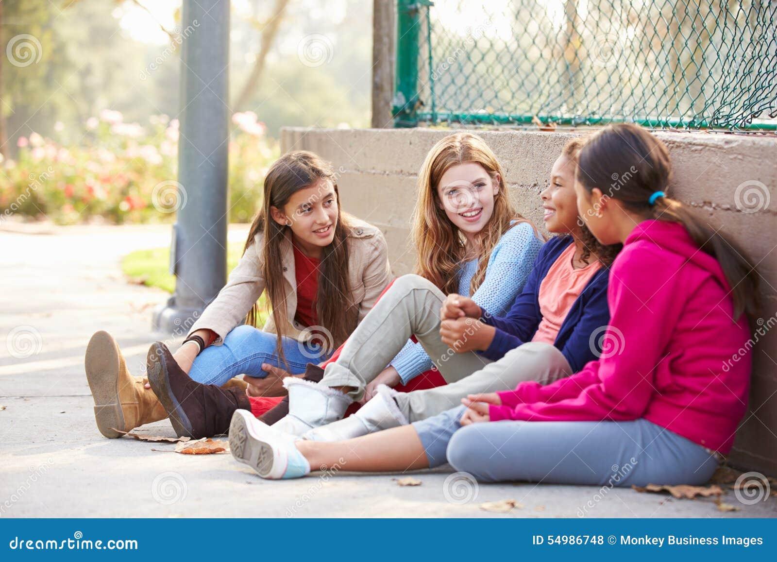 Fyra unga flickor som ut hänger i, parkerar tillsammans