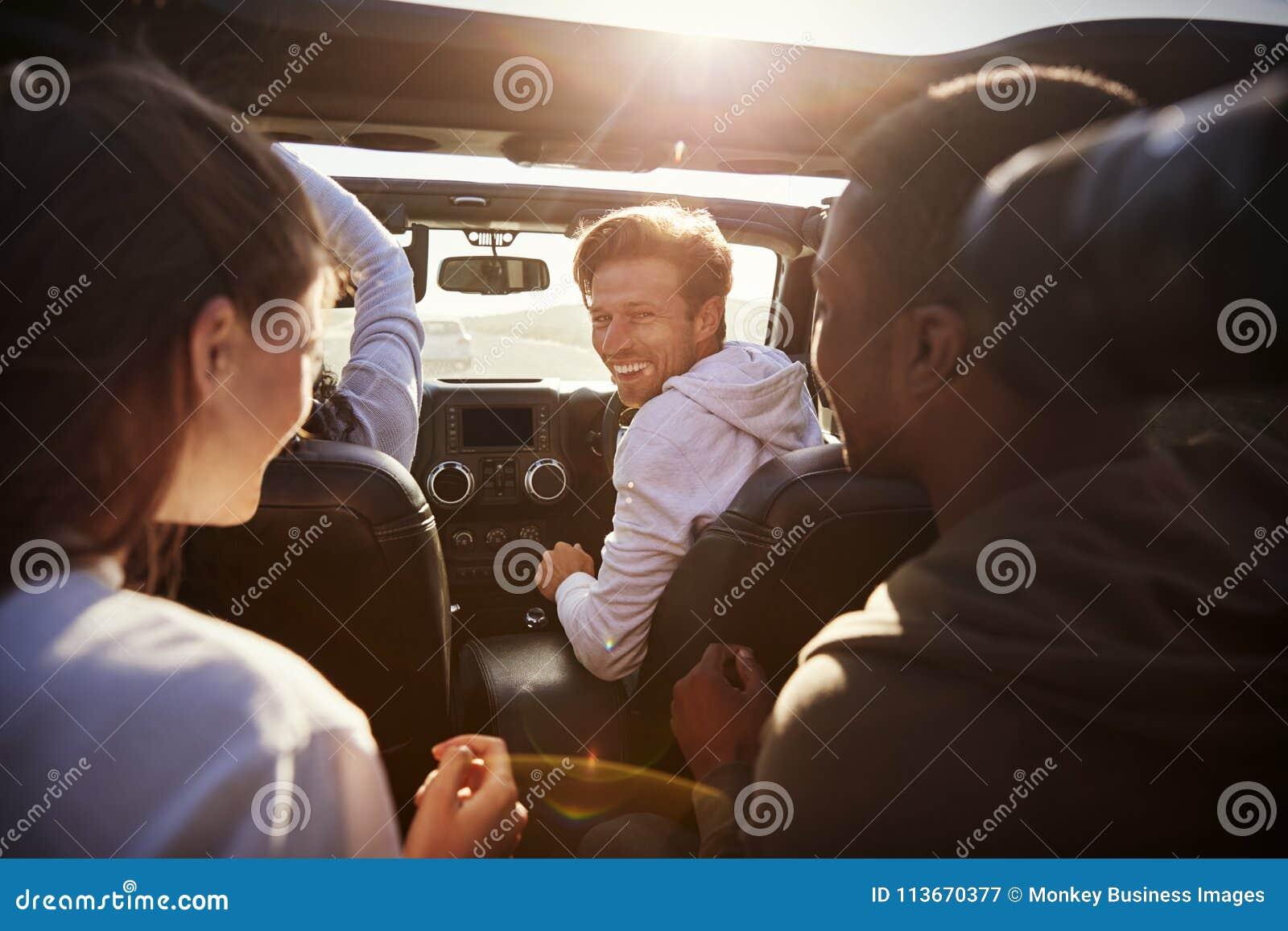 Fyra unga vuxna vänner tillsammans i en bil på en vägtur