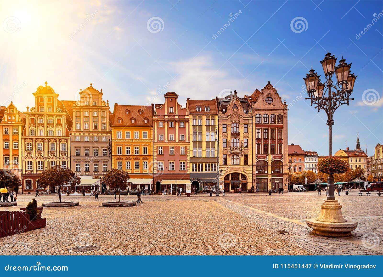Fyrkant för central marknad i Wroclaw Polen med gamla färgrika hus, gatalyktalampan och att gå turistfolk