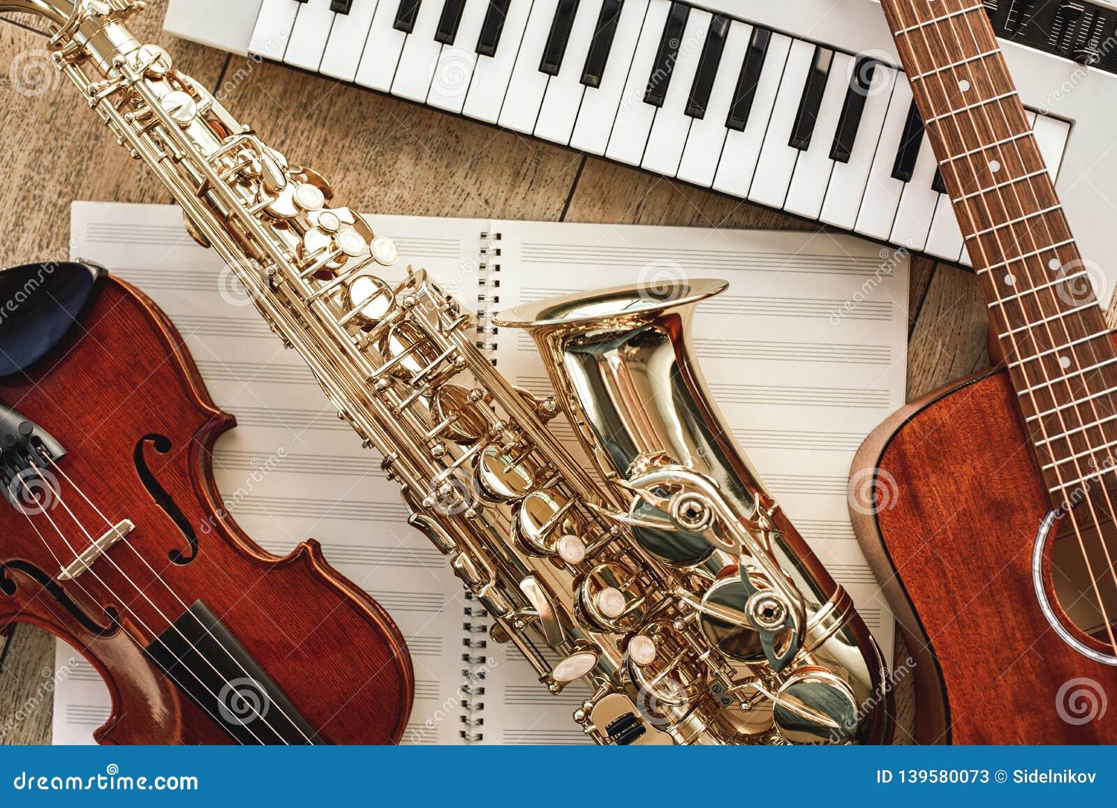 Fyrkant för sammansättningsmusikström Bästa sikt av musikinstrumentuppsättningen: synt, gitarr, saxofon och fiol som ligger på ar